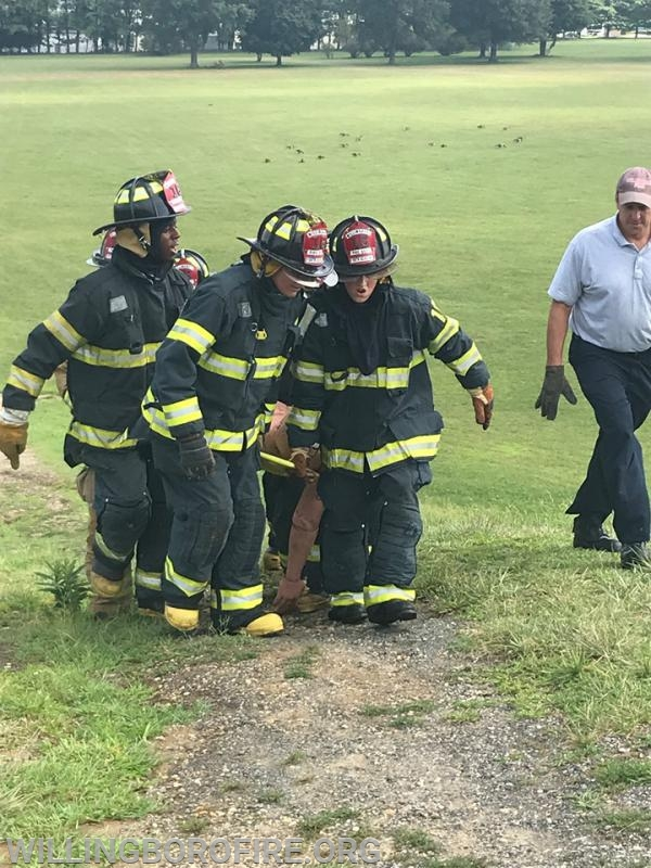A crew working together to carry a training mannequin up the hill at Mill Creek Park